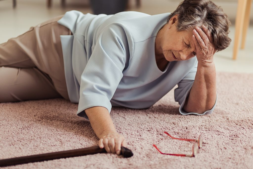 Senior woman with headache lying on the floor after a fall