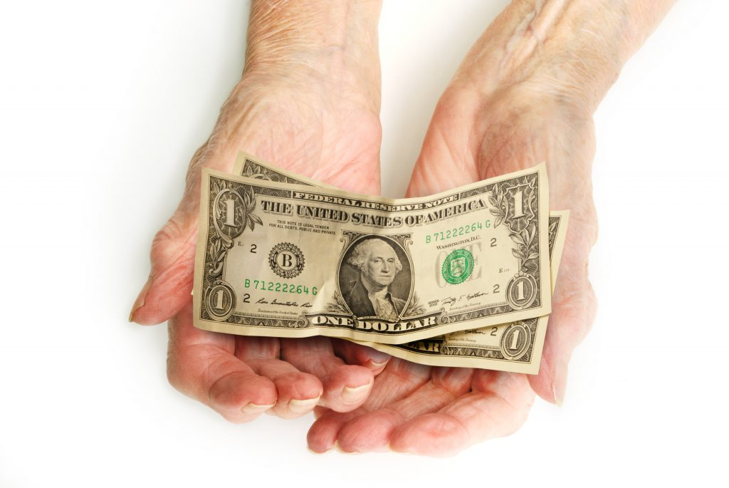 elderly woman's hands holding two, one dollar bills