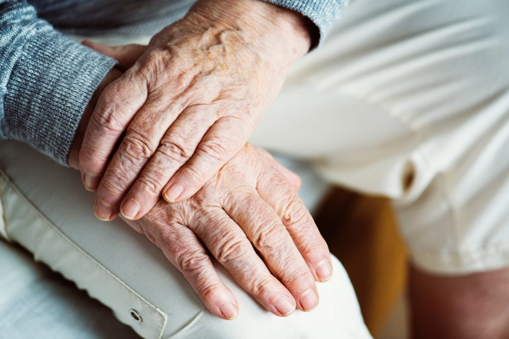 Elderly person's hands crossed and sitting on their knee.