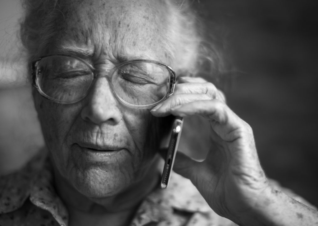 Elderly woman with eyes closed, holding phone to her ear