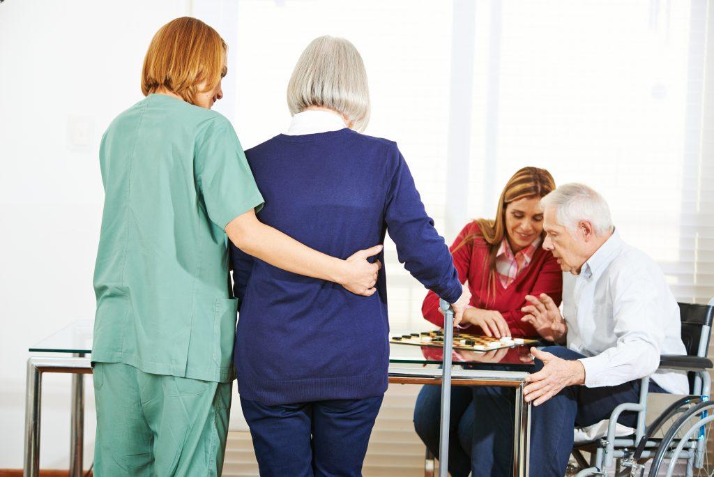 Woman nursing elderly people in retirement home